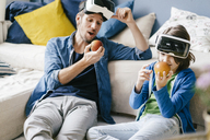 Father and son wearing VR glasses and eating apples at home - KNSF03595