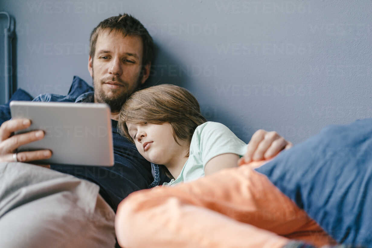 Father and son watching a movie on tablet at home - KNSF03607 - Kniel Synnatzschke/Westend61