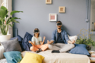 Father and son wearing VR glasses practicing yoga at home - KNSF03610
