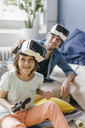 Portrait of happy boy and father wearing VR glasses playing video game at home - KNSF03613