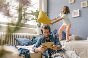 Father and son having a pillow fight at home - KNSF03616