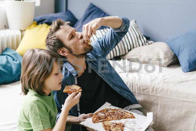 Father and son eating pizza at home - KNSF03619