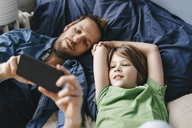 Father and son looking at smartphone together at home - KNSF03631