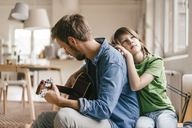 Son leaning against father playing guitar at home - KNSF03637