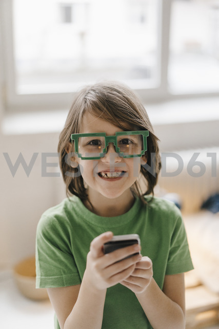 Portrait of smiling boy wearing pixel glasses holding cell phone - KNSF03640