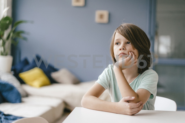 Portrait of sad boy sitting at table at home - KNSF03643