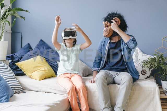 Father wearing monkey mask looking at son wearing VR glasses at home - KNSF03646