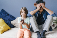 Father wearing monkey mask sitting next to son using smartphone at home - KNSF03649
