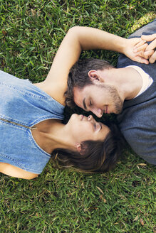 Overhead view of romantic couple lying on grass - CAVF27556