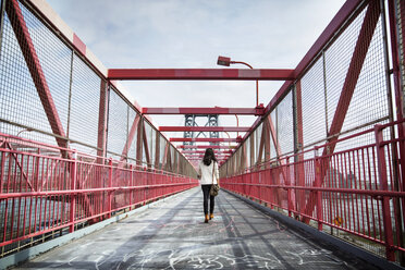 Rear view of young woman walking across Williamsburg Bridge - CAVF27577