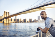 Side view of thoughtful male athlete standing on promenade with Brooklyn Bridge in background - CAVF27580