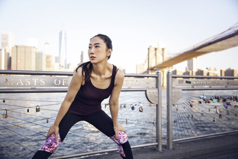 Thoughtful female athlete exercising on promenade with Brooklyn Bridge and One World Trade Center in background - CAVF27586
