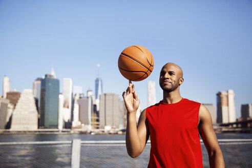 Smiling man spinning basketball on finger against city skyline - CAVF27592