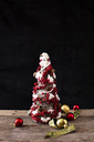 Close-up of artificial Christmas tree with baubles on wooden table against black background - CAVF27595