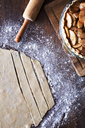 High angle view of dough by apple slices on wooden table - CAVF27604