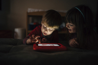 Happy siblings playing video game while lying on bed at home - CAVF27622
