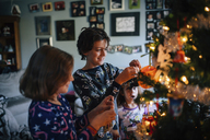 Siblings decorating Christmas tree at home - CAVF27625