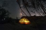 Illuminated tent on field against star field at night - CAVF27646