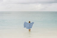 Rear view of girl holding towel walking towards sea against cloudy sky - CAVF27724
