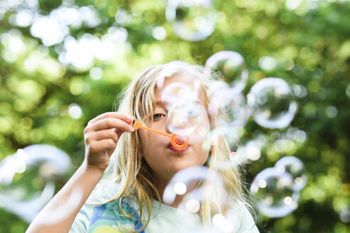 Girl blowing bubbles at park - CAVF27739