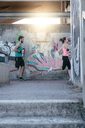 Side view of young couple jogging at bridge - CAVF27751