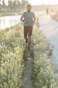Sportsman jogging amidst plants in park - CAVF27754