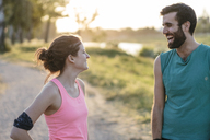 Happy couple standing face to face while exercising at park - CAVF27757