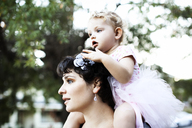 Thoughtful woman carrying baby girl on shoulders at park - CAVF27805