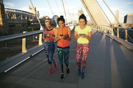 Smiling friends using phone while walking on bridge in city - CAVF27895