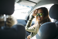 Smiling young woman wearing sunglasses sitting in car during winter - CAVF27910