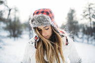 Close-up of woman wearing fur hat at snow covered field - CAVF27919