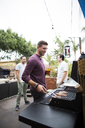 Man preparing food on barbecue grill while standing with friends in background - CAVF28006