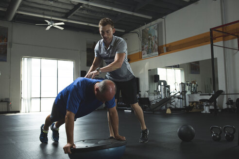 Trainer assisting customer while practicing push-ups on bosu ball with balance disc in gym - CAVF28027