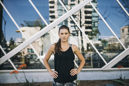 Portrait of confident female athlete standing with hands on hip in city - CAVF28051