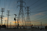 Low angle view of electricity pylons on road against sky during sunset - CAVF28108