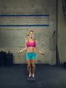 Portrait of confident female athlete skipping at gym - CAVF28237
