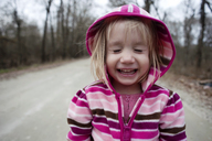 Close-up of smiling girl with eyes closed standing on road - CAVF28333