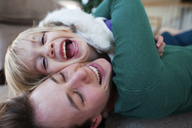 Happy mother embracing daughter while lying on carpet at home - CAVF28360