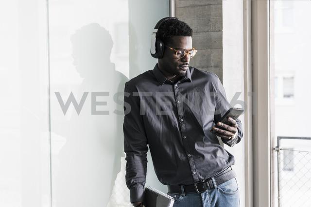 Businessman wearing headphones looking at cell phone - UUF13087