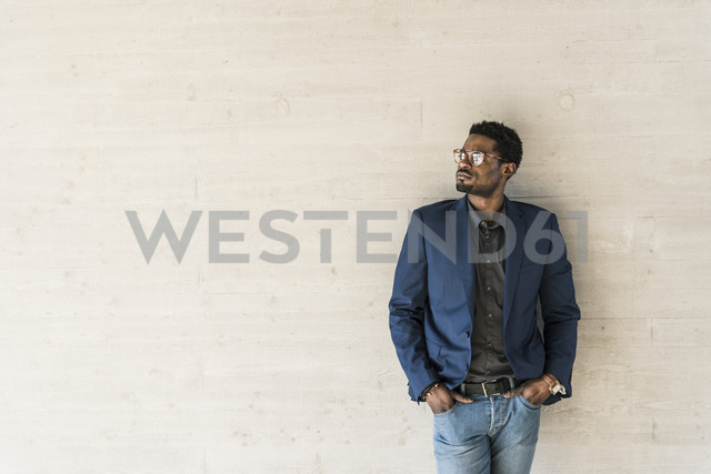Businessman standing at concrete wall looking away - UUF13093