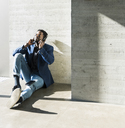 Businessman sitting on the floor in sunshine  wearing headphones - UUF13096