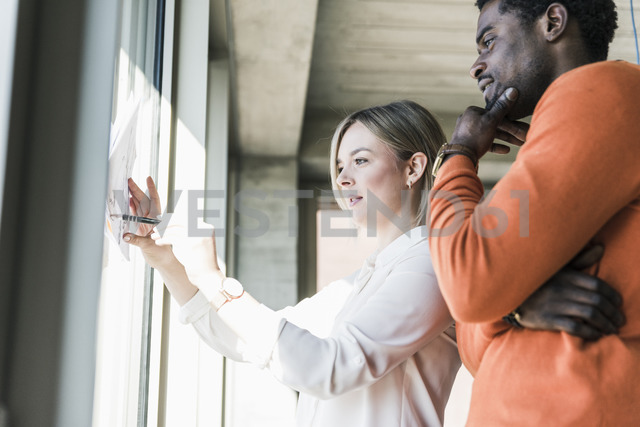 Casual businesswoman and businessman discussing paper at the window - UUF13111