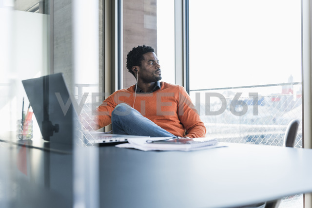 Casual businessman with earphones sitting at desk looking out of window - UUF13117
