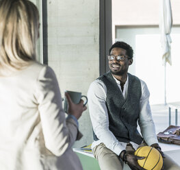 Businessman with basketball in office smiling at colleague - UUF13120