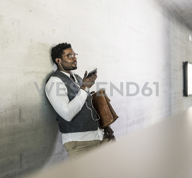 Businessman standing at concrete wall with earphones, cell phone and briefcase - UUF13123