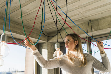 Young businesswoman in office examining cables at light bulbs - UUF13126