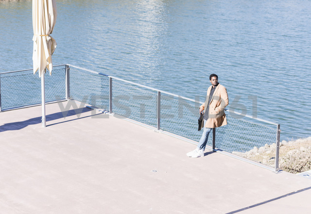 Businessman standing at the riverside with briefcase looking around - UUF13135