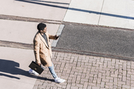 Businessman walking outdoors with briefcase, cell phone and earphones - UUF13138