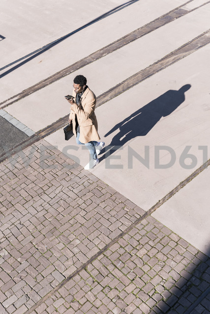 Businessman walking outdoors with briefcase, cell phone and earphones - UUF13141