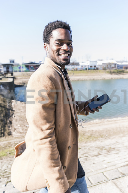 Portrait of smiling businessman at the waterfront with cell phone and earphones - UUF13144